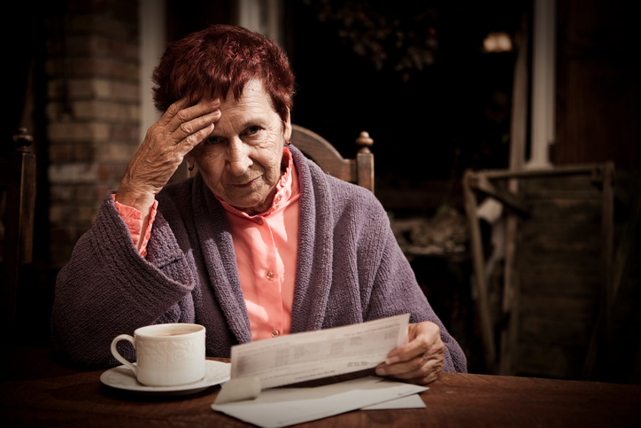 Older Woman Reading Bills, Worried About Debts of Deceased Spouse